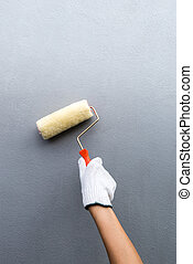 Hand glove holding painting roller white painting home wall