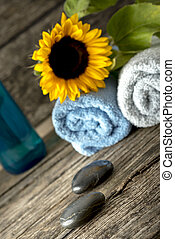 Spa setting with a towels, sunflower on top, massage stones, and a bottle of massage oil