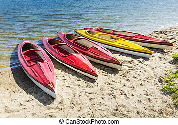 Colorful kayaks moored on lakeshore, Goldopiwo Lake, Mazury,...