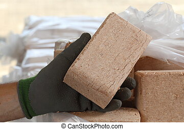 Worker with wood briquette in hand