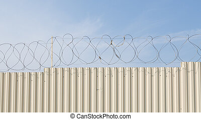 fence with barbed wire - barbed wire on top of the white...