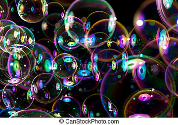 rainbow colors of flying soap bubbles on black background