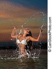 Sexy brunette woman in wet swimsuit