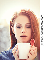 women with white cup of coffee - Young redhead women with...