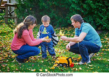 father, mother and young son at a picnic in the park