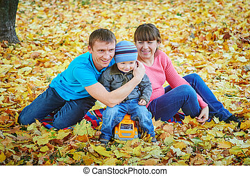 Young family walking in autumn park