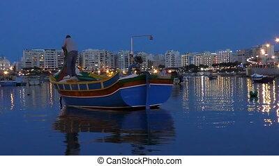 Man in traditional boat in Malta - Beautiful evening night...