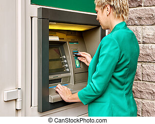 Business woman operates ATM - Business woman operates an ATM...