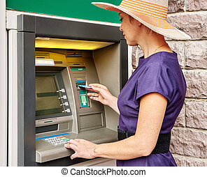 Pretty woman operates ATM - Pretty woman operates an ATM on...