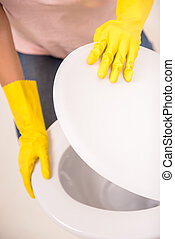 Cleaning the toilet - Woman with a rubber glove cleans a...