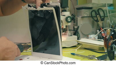 Removing broken touchscreen - Close-up shot of man using...