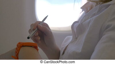 Woman using smart watch in plane - Woman passenger using...