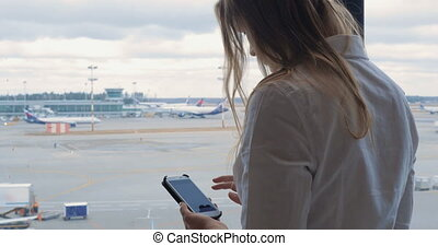 Woman texting on cell and looking at airport area - Young...