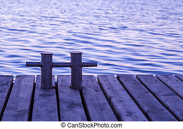 Rusty bollard on wooden pier with empty space for text