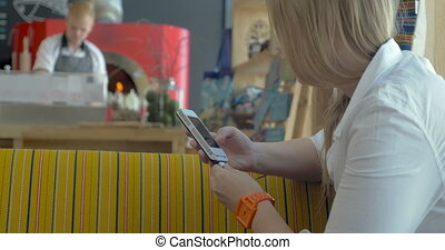 Woman with smart phone in pizzeria restaurant - Young woman...