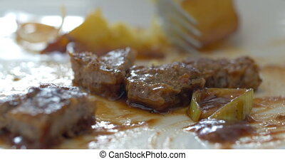 Eating a dish with meat and potatoes - Close-up shot of...