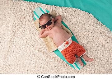 Newborn Baby Boy Sleeping on a Surfboard - Newborn baby boy...