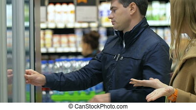 Young couple arguing on taking ice-cream in the store