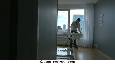 Man ironing the clothes at home - Steadicam shot of a youg...