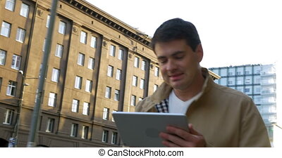 Man using tablet computer on the go in city - Steadicam shot...