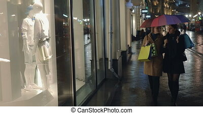 Evening shopping in rainy city - Two female friends with...