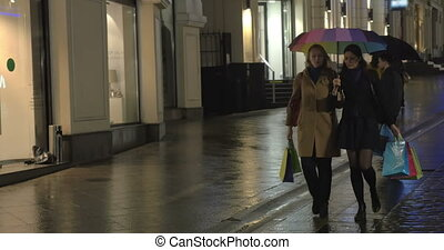 Girls having a walk and talk after shopping in the evening city