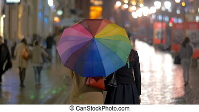 City walk under colorful umbrella in rainy evening
