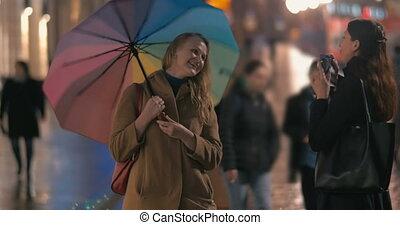 Happy friends making photos using retro camera in rainy city...