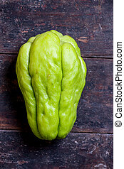 Chayote - Green chayote is on the old wooden background.