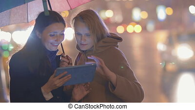 Friends Using Tablet PC Outdoors - Two female friends are...
