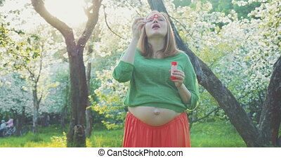 Pregnant Woman Blowing Soap Bubbles