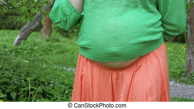 Pregnant woman smoothing belly outdoor - Steadicam shot of a...