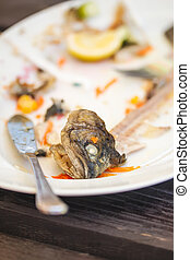 Plate with leftover bones of fish - Plate with food leftover...