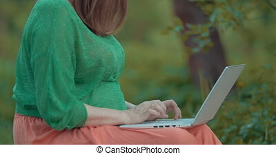 Pregnant woman working with laptop outdoor