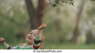 Little child taking efforts to reach the tree branch - Cute...