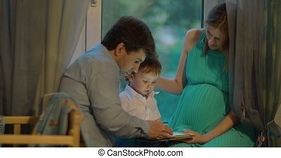 Boy Shows Something in Tablet to His Parents