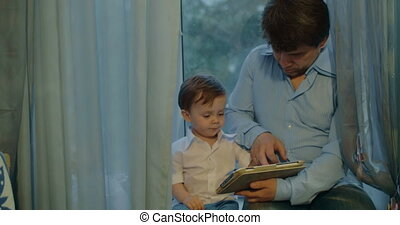 Father and Son Watching Cartoons in Tablet - Father and...