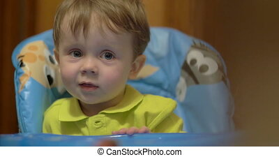 Lovely smiling boy sitting at feeding table - Portrait of...