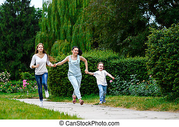 Happy Mother with daughter and son running on grass smiling.