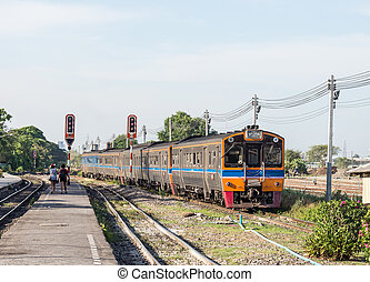 Diesel railcar set is going to train station in Thailand.