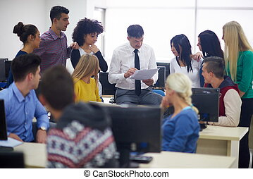 students with teacher in computer lab classrom - group of...