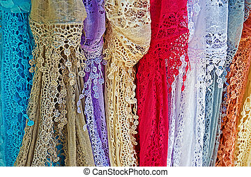 Colored lace scarves hanging and exposed for sale.