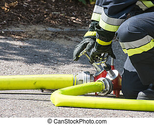 Fireman at work - Fireman operating the valve of a firehose