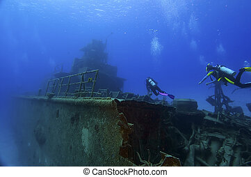 Diving on a wreck - Two divers are swimming towards the...