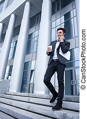 Handsome young businessman is going out from his office -...