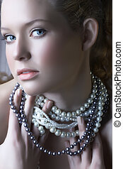 blond beauty in pearls - beautiful woman with blue eyes in...