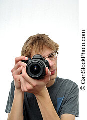 Young teenage boy holding Digital SLR Camera and pointing it...