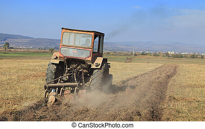 Ploughing - Image of a field with a tractor ploughing.