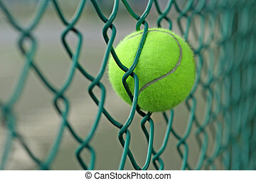 tennis ball in the chainlink behind court - tennis ball in...