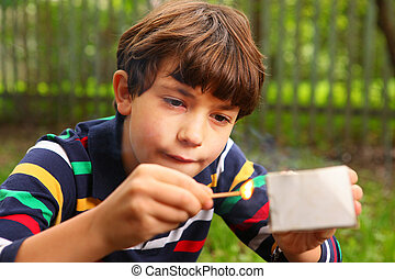 preteen handsome boy play with box of matches - preteen...